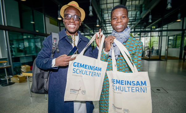 Two men pose with jute bags from Engagement Global for a photo.