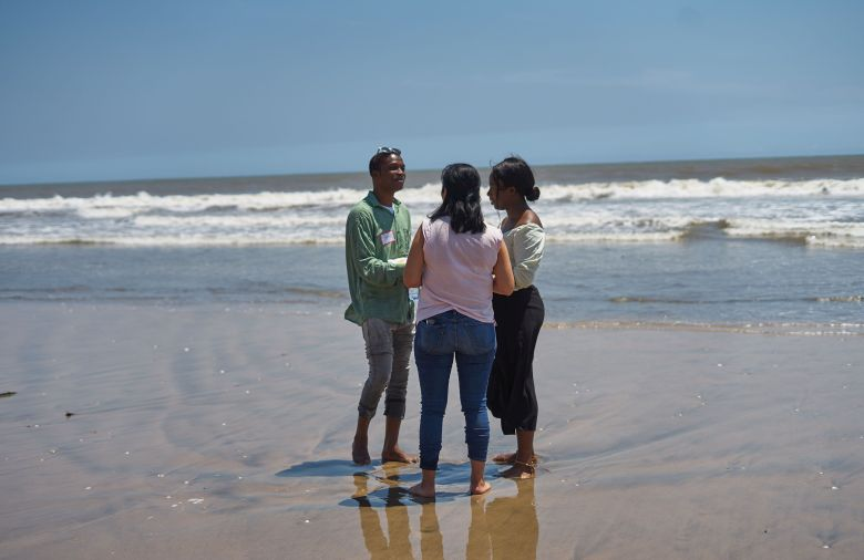 Three persons standing on the beach