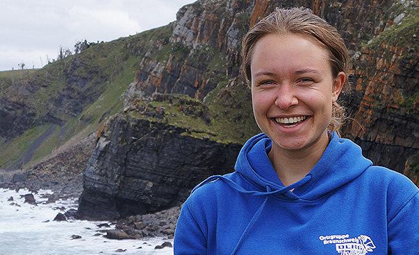 A young woman wearing a blue hoodie and holding a camera looks into the camera and laughs. The sky in the background is cloudy and the sea and cliffs are visible.