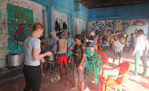 Young people in the Babawatoto Centre for children and youth are teaching artistry to the German group of visitors.