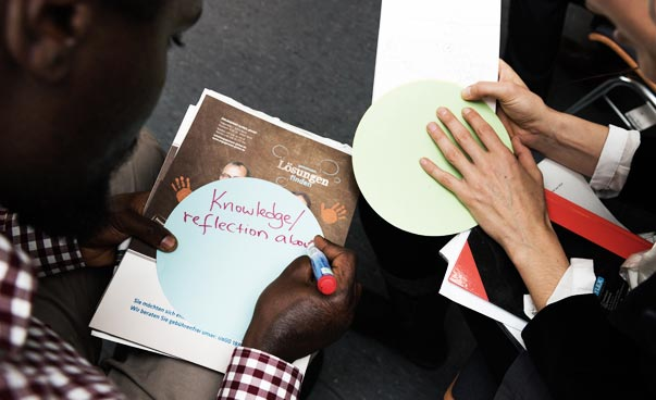 ": A man writes ""Knowledge/reflection about"" on a circular paper. Another person has more notes ready. Both persons are only partially visible. The camera captures the situation from above."